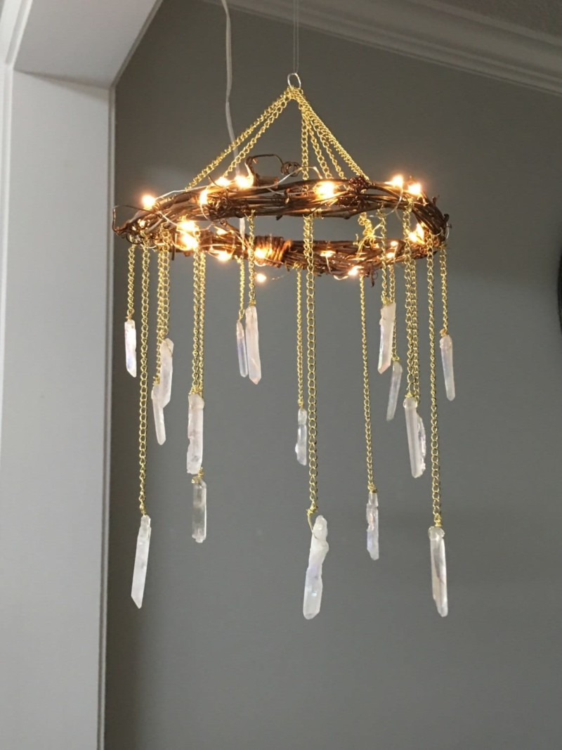 Bohemian Wood & Crystal Chandelier: This rustic wood chandelier with crystals is the perfect piece to light up your home, wedding venue, nursery or yoga studio. The dainty soft lights help to create a romantic soft ambiance to your space. Envision adding this piece to your outdoor wedding, favorite reading nook or adding that finishing touch to your bedroom or child\'s playroom. #bedroomdecor #chandelier #handmadelighting #lightingdesign #rusticlighting #woodworking #woodlamp #farmhousedecor